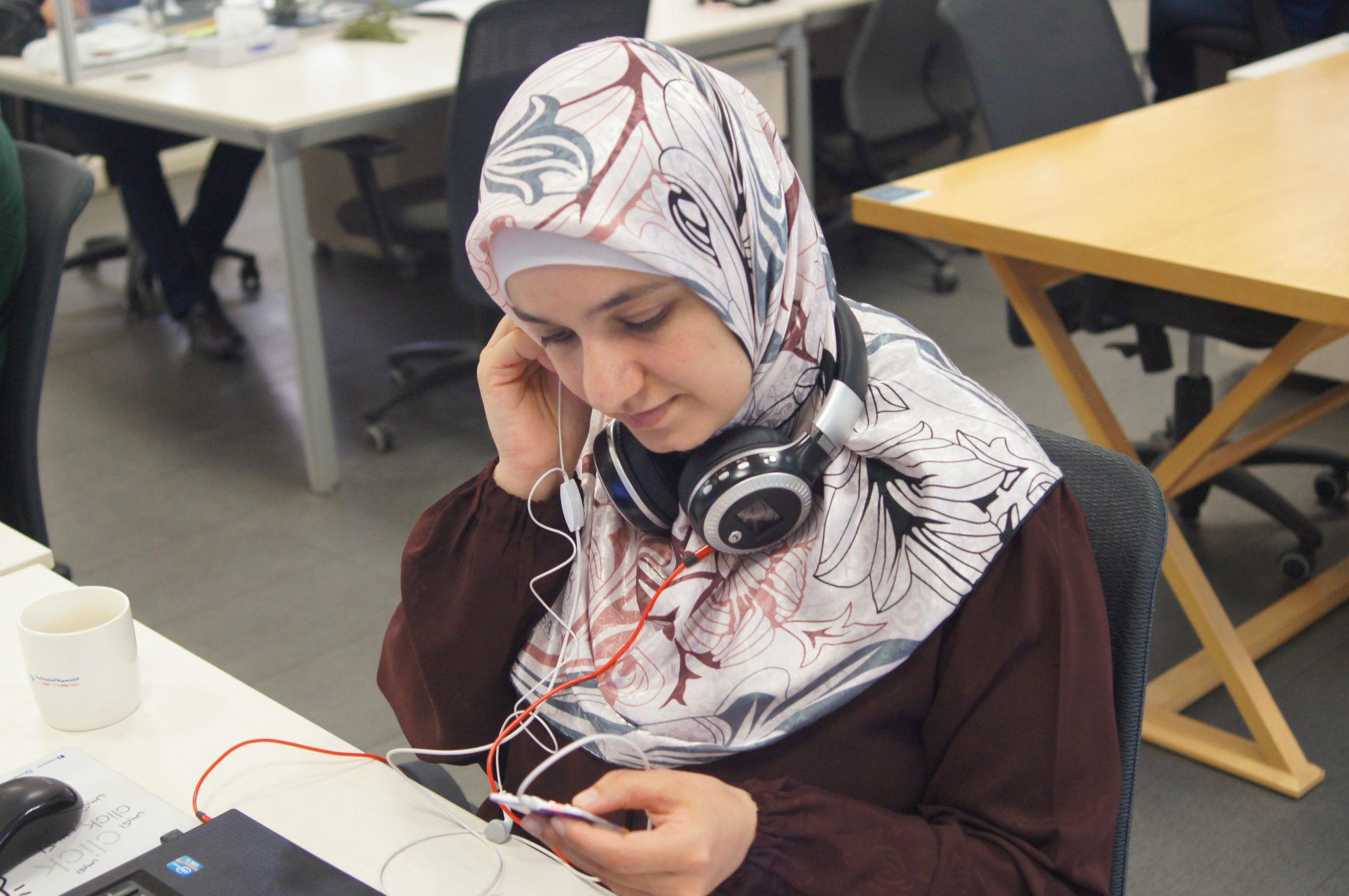 """آلاء سليمات- شريك مؤسس ومديرة تنفيذية لشركة مسموع - تختبر أحد الأجهزة  المستخدمة  في الإصغاء لكتاب """"مسموع"""" باستخدام تقنية MP3  للتسجيل"""
